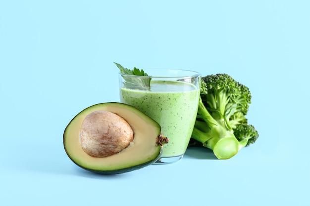 Bicchiere di frullato sano con avocado e broccoli sulla superficie del colore