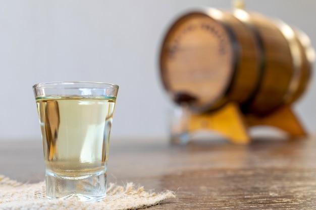 Bicchiere di alcol distillato di alta qualità e vecchia botte di rovere sfocata