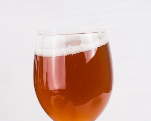 Bicchiere di birra artigianale fatta in casa e sacchetto di malto leggero su sfondo bianco.