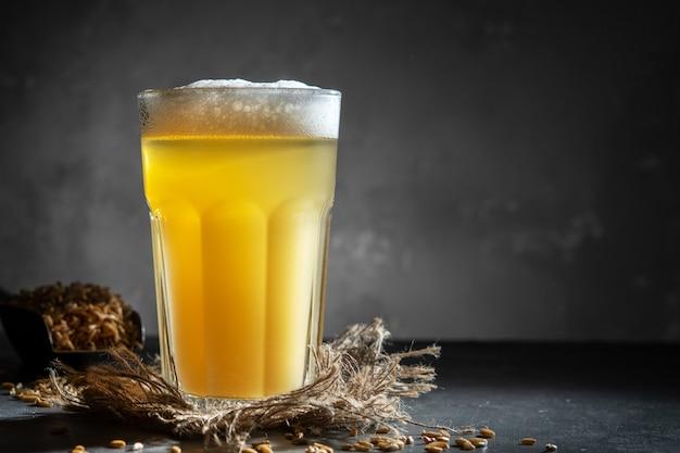 Bicchiere di birra fatta in casa su uno sfondo di cemento. bicchiere di birra artigianale su uno sfondo scuro.