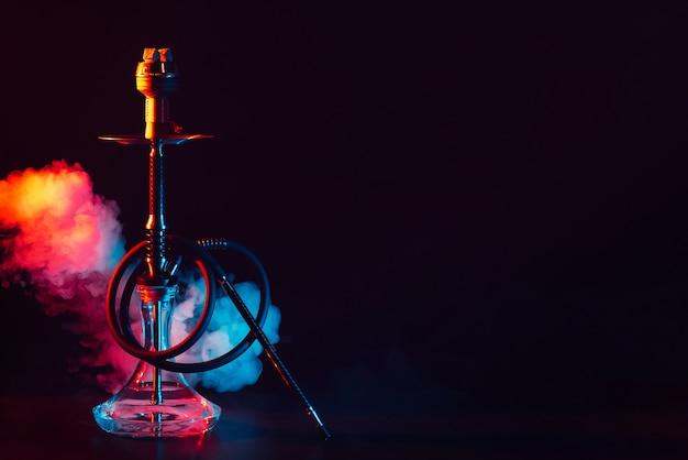 Narghilè di vetro con una ciotola di metallo sul tavolo su uno sfondo nero con fumo e luci al neon colorate