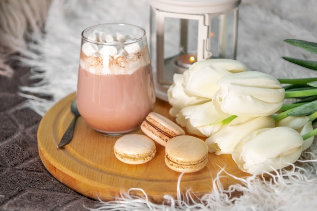 Un bicchiere di cioccolata calda con marshmallow, torte di maccheroni e tulipani bianchi su un vassoio a letto da vicino