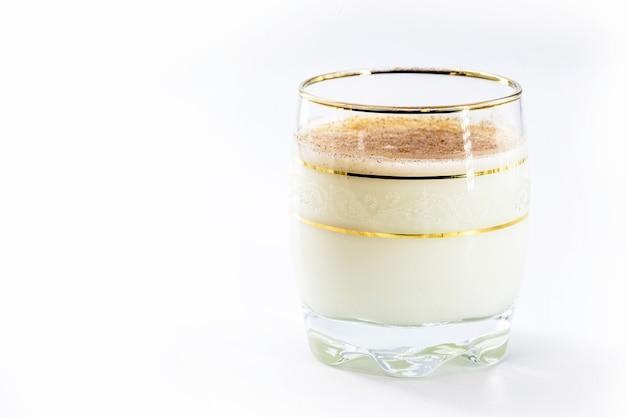 Bicchiere di zabaione caldo, bevanda natalizia, a base di uova, cannella, mandorle e liquore al rum. sfondo bianco isolato e copia spazio.