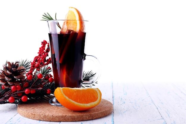 Bicchiere di vin brulé caldo con pezzi di arancia sul tappeto e tavolo in legno colorato sullo sfondo