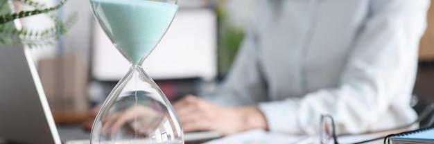 Clessidra di vetro che sta contro il fondo della donna che lavora al primo piano del computer portatile
