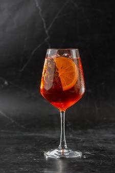 Bicchiere di cocktail aperol spritz ghiacciato servito in un bicchiere da vino decorato con fettine di arancia
