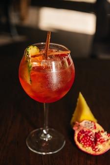 Bicchiere di cocktail aperol spritz ghiacciato servito in un bicchiere di vino con ananas e granato, posto su un tavolo nel ristorante