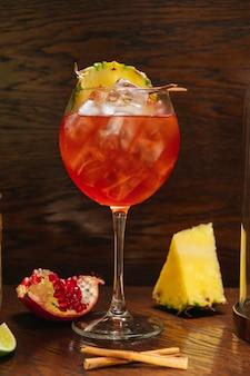 Bicchiere di aperol spritz ghiacciato servito in un bicchiere da vino con ananas e granato