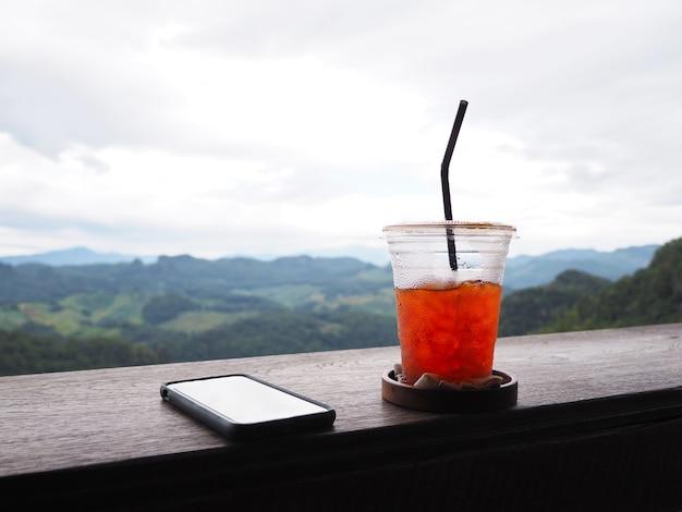 Bicchiere di tè freddo e smartphone sulla tavola di legno d'epoca sopra la foresta verde sulla montagna con sfondo cielo piovoso.