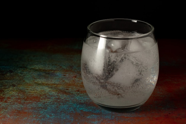 Bicchiere di acqua ghiacciata riempito con acqua gassata fredda su uno sfondo scuro