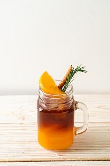 Un bicchiere di caffè nero americano ghiacciato e uno strato di succo di arancia e limone decorato con rosmarino e cannella su fondo di legno
