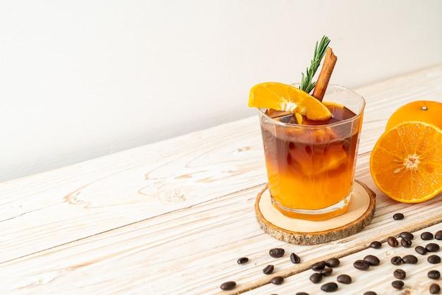 Un bicchiere di caffè nero americano ghiacciato e uno strato di succo d'arancia e limone decorato con rosmarino e cannella su una fetta di legno