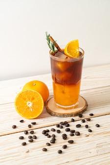 Un bicchiere di caffè nero americano ghiacciato e uno strato di succo d'arancia e limone decorato con rosmarino e cannella sulla superficie del legno
