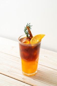 Un bicchiere di caffè nero americano ghiacciato e uno strato di succo di arancia e limone decorato con rosmarino e cannella sulla superficie del legno