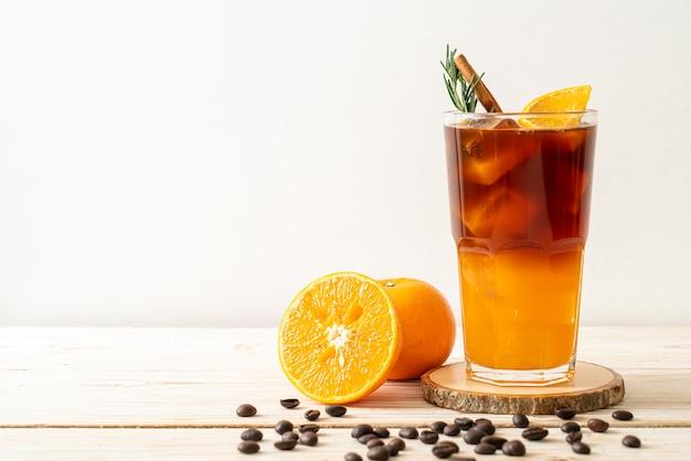 Un bicchiere di caffè nero americano ghiacciato e uno strato di succo d'arancia e limone decorato con rosmarino e cannella sul tavolo di legno