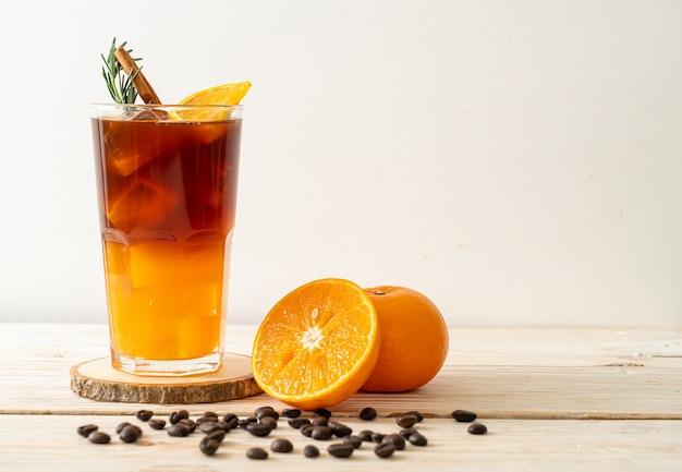 Un bicchiere di caffè nero americano ghiacciato e uno strato di succo di arancia e limone decorato con rosmarino e cannella su un tavolo di legno