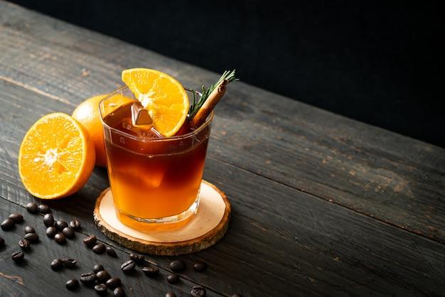 Un bicchiere di caffè nero americano ghiacciato e uno strato di succo d'arancia e limone decorato con rosmarino e cannella