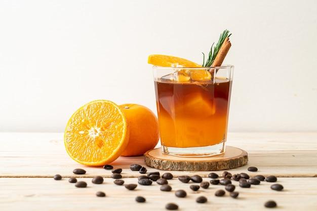 Un bicchiere di caffè nero americano ghiacciato e uno strato di succo di arancia e limone decorato con rosmarino e cannella