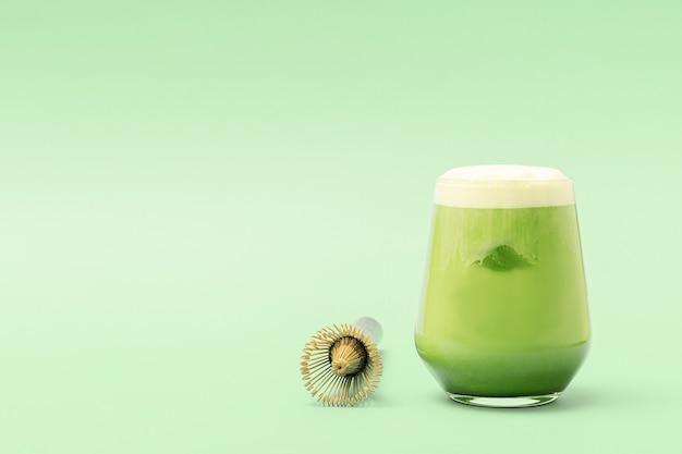 Un bicchiere di latte matcha ghiacciato su uno sfondo verde con spazio di copia.