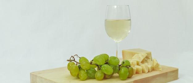 Un bicchiere di vino bianco italiano servito con parmigiano e uva su un tagliere di legno con fondo bianco