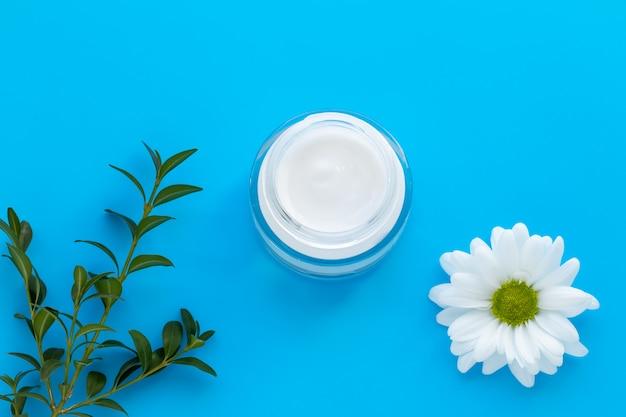 Barattolo di vetro di crema facciale con la camomilla bianca su fondo blu, concetto di cura di pelle.