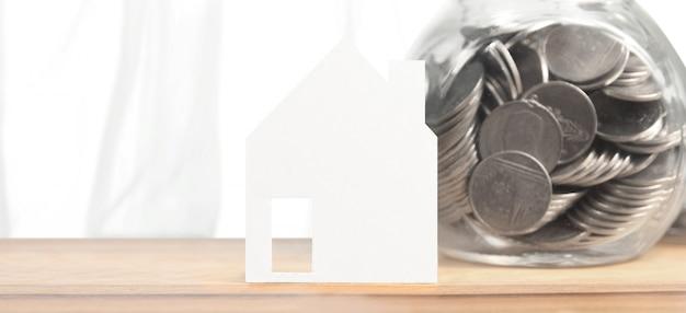 Vaso di vetro pieno di monete e modello di casa