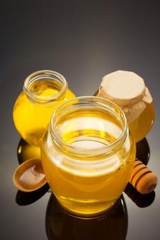 Vaso di vetro pieno di miele sul nero