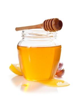 Vaso di vetro pieno di miele e mestolo isolato su bianco
