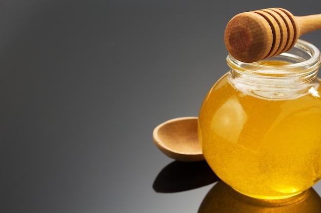 Vaso di vetro pieno di miele e bastone sul nero