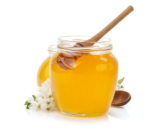 Vaso di vetro pieno di miele e bastone isolato su bianco