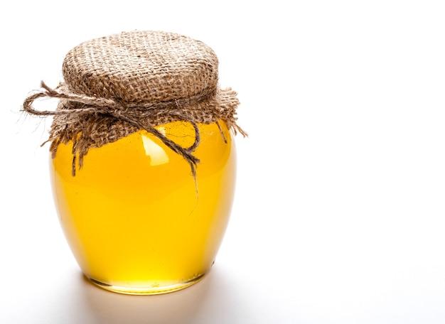 Vaso di vetro pieno di miele su uno sfondo bianco