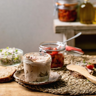 Vaso di vetro di patè di fegato di pollo fatto in casa con pane di segale a fette, pomodori secchi e insalata di germogli verdi sul tavolo da cucina in legno. colazione o aperitivo casalingo. immagine quadrata