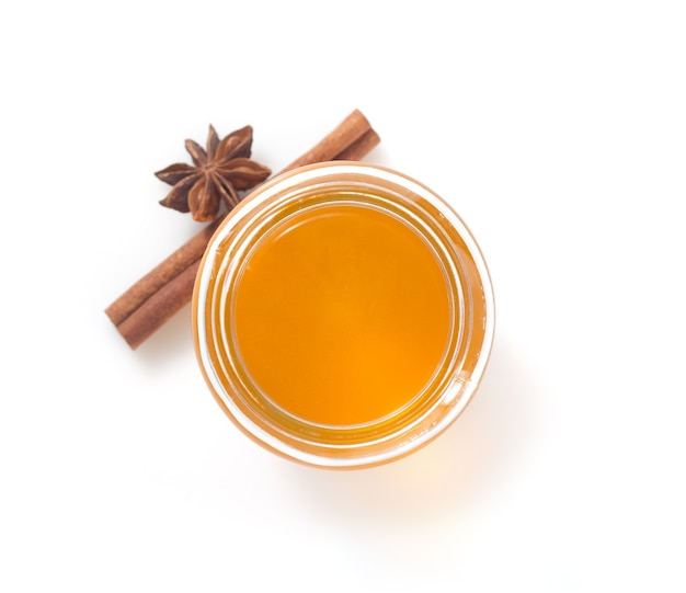 Vaso di vetro di miele isolato su bianco