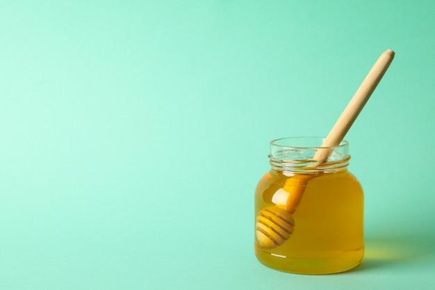 Vasetto di vetro di miele con mestolo su sfondo di menta, spazio per il testo