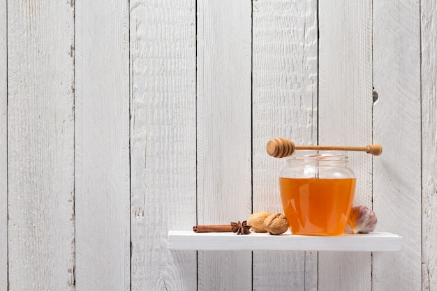 Vaso di vetro di miele sullo sfondo dello scaffale in legno