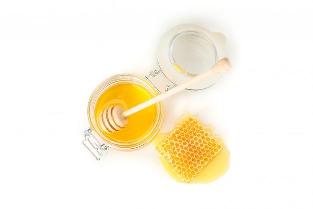 Vaso di vetro, nido d'ape e mestolo isolato su sfondo bianco