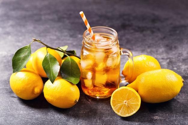 Vaso di vetro di tè freddo con limoni freschi su oscurità