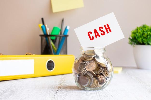 Il barattolo di vetro è pieno di monete. sopra, sulla banca c'è una carta con la scritta cash. bilancio di investimento.