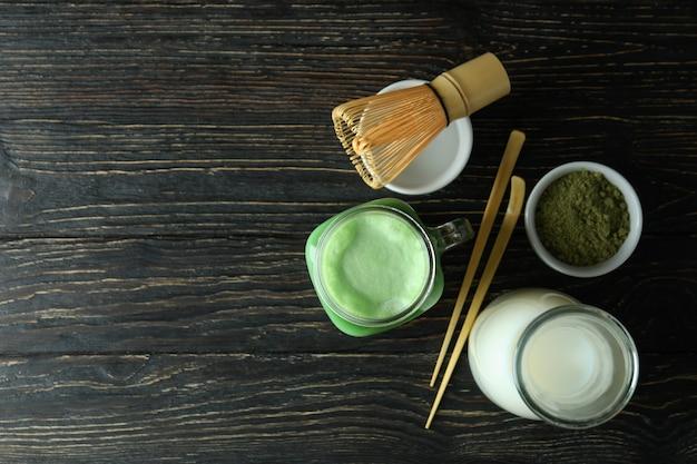Barattolo di vetro di latte matcha e accessori da realizzare su fondo in legno