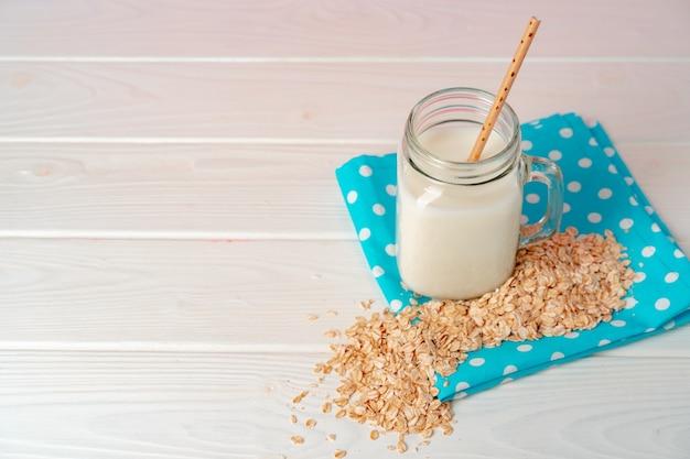 Vaso di vetro di latte vegano di avena con fiocchi di avena sul tavolo di legno bianco
