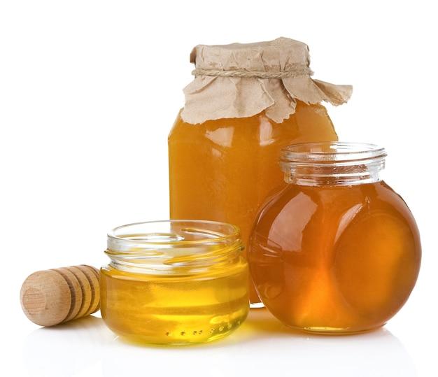 Vaso di vetro e vaso di miele con il bastone isolato su bianco