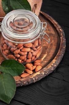 Vaso di vetro con mandorla su tavola di legno, sfondo nero. cibo vitaminico