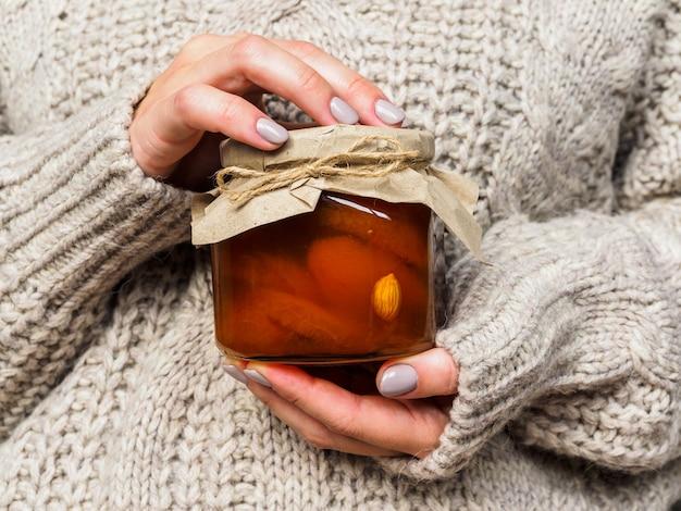 Vaso di vetro con marmellata di albicocche nelle mani delle ragazze