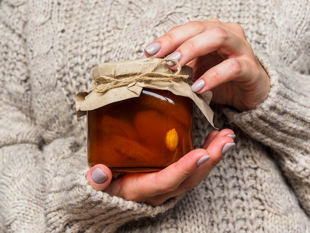 Vaso di vetro con marmellata di albicocche nelle mani di una donna