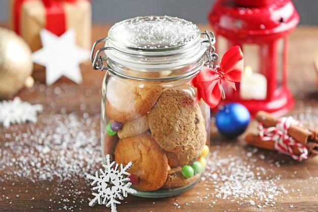 Vaso di vetro con biscotti di natale sulla tavola di legno