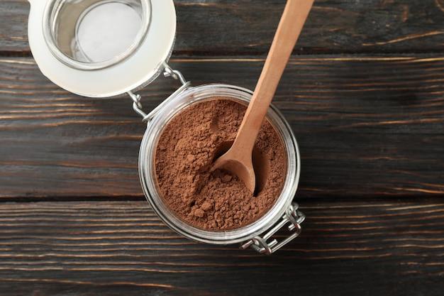 Barattolo di vetro con cacao in polvere e cucchiaio su legno, fine su