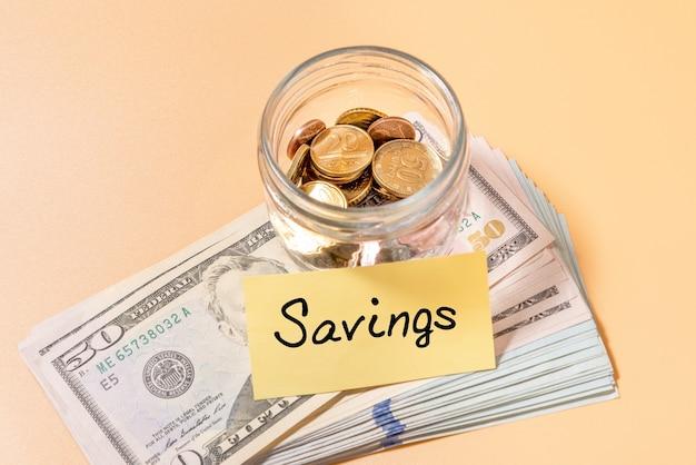 Barattolo di vetro con monete e banconota da 50 dollari con etichetta risparmio. concetto finanziario.