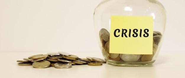 Vaso di vetro con monete. l'iscrizione sul foglio per appunti crisis. concetto finanziario.