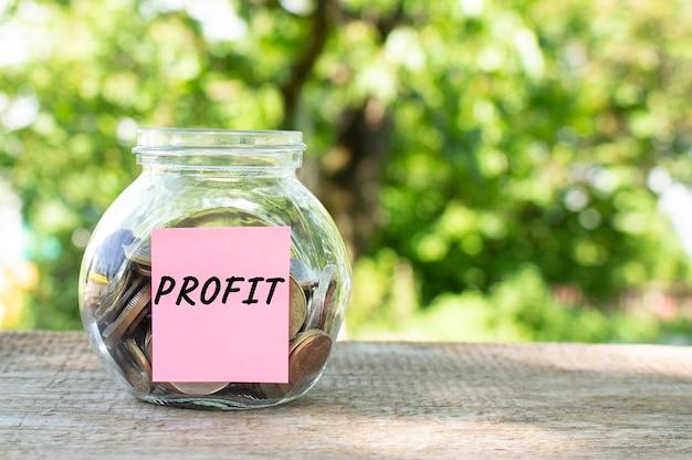 Un barattolo di vetro con monete e la scritta profit su un tavolo di legno. budget per investire.
