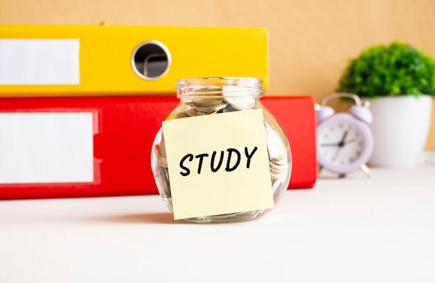 Sul tavolo da lavoro c'è un barattolo di vetro con delle monete. c'è un adesivo sulla banca con il testo studio.